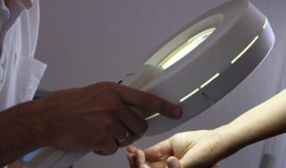 Bei der Hautkrebs-Früherkennung wird beim Dermatologen mit einem Vergrößerungsglas die Haut nach Veränderungen abgesucht. (Foto)
