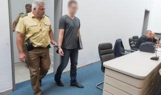 Der Angeklagte Christian A. wird von einem Polizeibeamten in den großen Sitzungssaal des Landgerichts in Ingolstadt geführt. (Foto)