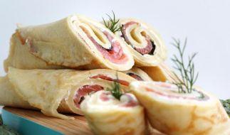 Sind schnell gemacht und liegen gut in der Hand: Pfannkuchen werden mit Räucherlachs, Frischkäse und Dill zu kleinen Snacks gerollt. (Foto)
