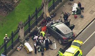 Das Standbild aus einem Video zeigt Hilfskräfte, die am 22.03.2017 in der Nähe des britischen Parlaments in London (Großbritannien) neben einem Auto einen Verletzten behandeln. (Foto)