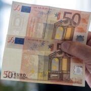Ein echter (oben) und ein gefälschter, alter 50-Euro-Schein.