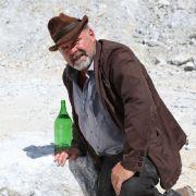 Kurz bevor Anton erschossen wird, baut er eine Flasche als Zielscheibe auf.
