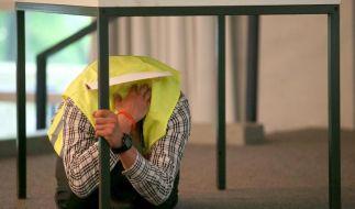 In einem Gebäude sucht man sich am besten Schutz unter stabilen Möbeln oder Türrahmen. (Foto)