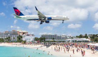 Am Maho Beach auf Sint Maarten fliegt ein Flugzeug besonders dicht über die Badegäste hinweg auf die Landebahn des Fluhafens zu. (Foto)