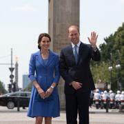 Adrett gekleidet, freundlich lächelnd und winkend grüßen William und Kate vom Brandenburger Tor. Kates blaue Clutch von Jimmy Choo ist übrigens längst ausverkauft.