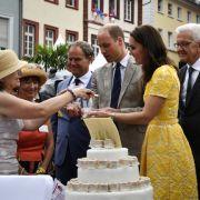 Die britischen Royals erhalten auf einem deutsch-britischen Markt in der Altstadt von Heidelberg ein Stück von einer riesigen Torte.