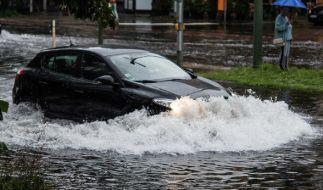 Ein Pkw fährt am 22.07.2017 in Berlin nach einem Gewitter und starken Regenfällen durch die Wassermassen in der Breiten Straße. (Foto)