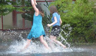 Zwei junge Frauen springen am 22.07.2017 durch vom Regen überschwemmte Wege in Hennigsdorf (Brandenburg). (Foto)