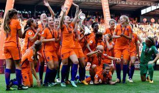 Die Spielerinnen aus den Niederlanden jubeln mit dem Pokal über ihren Sieg. (Foto)