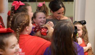 Stürmische Begrüßung: Meghan Markle wird von Kindern umarmt bei ihrem gemeinsamen Besuch mit Prinz Harry in Wales. (Foto)