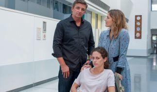 Sandra (Anja Knauer, M.) wird nach ihrer Untersuchung bei Dr. Martin Gruber (Hans Sigl, l.) von ihrer Schwester Christina (Morgane Ferru, r.) abgeholt. (Foto)