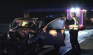 Ein Polizist steht auf der Autobahn 1 neben einem bei einem Unfall schwer beschädigten Auto und Macht ein Foto. (Foto)