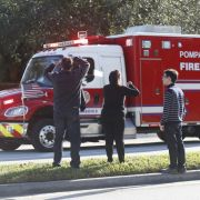 Verzweifelte Angehörige stehen neben einem Rettungsfahrzeug.