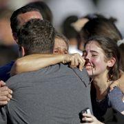Eine Familie fällt sich wiedervereint in die Arme.