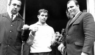 Justizbeamte begleiten Jürgen Bartsch (M) am 22.6.1966 aus der Polizeistation in Mettmann. Er lockte Kinder in einen unterirdischen Stollen, um sie auf unbeschreibbare Weise zu Tode zu quälen. (Foto)