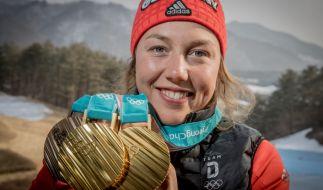Laura Dahlmeier zeigt stolz ihre drei olympischen Medaillen. (Foto)