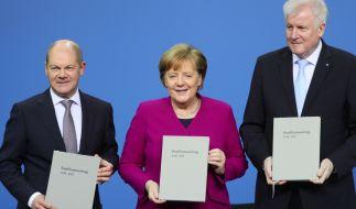Bundeskanzlerin Angela Merkel (CDU), der CSU-Vorsitzende Horst Seehofer und der kommissarische SPD-Vorsitzende Olaf Scholz zeigen den unterzeichneten den Koalitionsvertrag. (Foto)