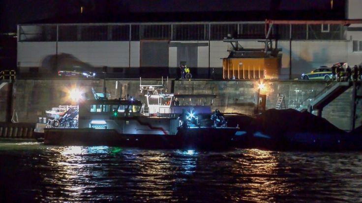 Mit Scheinwerfern wird von einem Schiff aus die Unfallstelle ausgeleuchtet, an der ein junger Radfahrer in den Rhein stürzte und ertrank.