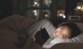 Eine Frau liegt im Bett und starrt auf ihr Smartphone. (Foto)