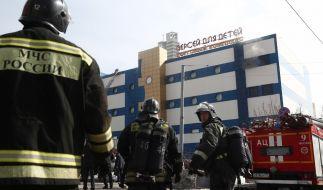 Feuerwehrleute stehen vor dem Einkaufszentrum «Persej dlja detej» (Perseus für Kinder), in dem ein Feuer ausgebrochen ist. (Foto)