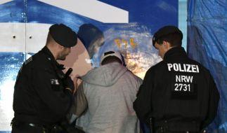 Polizisten durchsuchen einen Verdächtigen vor einem Essener Lokal. (Foto)