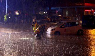 In Aachen sind zwei Feuerwehrleute auf einer überfluteten Straße im Einsatz. (Foto)
