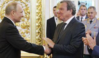 Gerhard Schröder (r), ehemaliger deutscher Bundeskanzler, gibt Wladimir Putin (l), Präsident von Russland, bei dessen Amtseinführung im Kreml die Hand. (Foto)