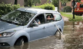 Fahrzeuginsassen kippen eingelaufenes Wasser aus ihrem Auto zurück auf die überflutete Straße in Hamburg-Bergedorf. (Foto)