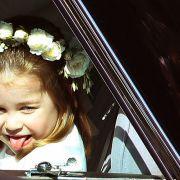Prinzessin Charlotte streckt im Auto ihre Zunge heraus.
