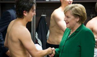 Oben ohne vor dem Staatsoberhaupt: Angela Merkel gratuliert Mesut Özil nach einem Sieg in der Kabine. (Foto)