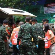 Rettungskräfte transportieren einen der Jungen, der in einer Höhle gefangen war, auf einer Liege, um ihn in ein Krankenhaus zu bringen.