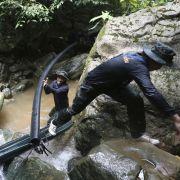 Thailändische Soldaten legen Schläuche mit Hilfe derer Wasser aus der Höhle fließen soll.