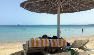 Eine Frau und ein Mann entspannen in Liegestühlen unter einem Sonnenschirm an einem öffentlichen Strand im ägyptischen Hurghada. Vor wenigen Tagen wurden in dem beliebten Urlaubsort zwei tote Hotelgäste aufgefunden. (Foto)