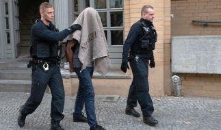 Polizisten führen einen verdächtigen Mann nach einer Razzia gegen kriminelle Mitglieder arabischer Großfamilien in der Pohlstraße ab. (Foto)