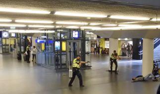 Polizisten richten ihre Waffen auf einen 19-jährigen Mann, der von der Polizei angeschossen wurde, nachdem er zwei Personen im Hauptbahnhof von Amsterdam niedergestochen hatte. (Foto)