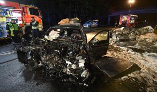 Einsatzkräfte stehen neben dem Autowrack, in dem zwei Menschen verbrannten. (Foto)