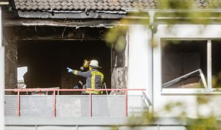 Kriminalbeamte stehen in einer ausgebrannten Wohnung im Hamburger Stadtteil Eißendorf. Hier griff zuvor ein 28 Jähriger drei Behördenmitarbeiter mit einem Brandsatz an. (Foto)