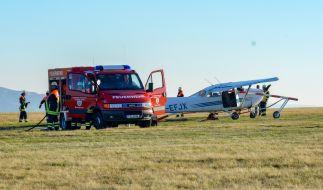 Feuerwehrleute stehen nach dem Flugunfall in Hessen neben dem verunglückten Sportflugzeug. (Foto)