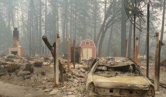 """USA, Paradise: Ein ausgebrannter Pkw und Trümmer nach dem Waldbrand, dem sogenannten """"Camp""""-Feuer. (Foto)"""