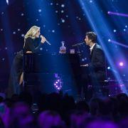 Florian David Fitz sitzt an einem schwarzen Flügel und singt gemeinsam mit Helene Fischer.