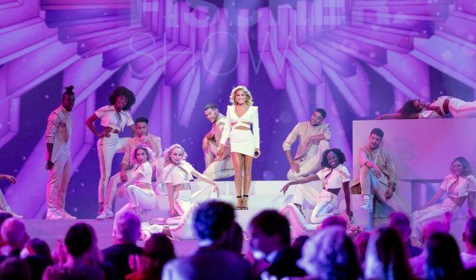 Helene Fischer steht in der Bühnenmitte auf einem weißen Podest. Dabei wird sie umringt von ihren Tänzerinnen und Tänzern. Alle tragen weiße Kleidung und lachen in die Kamera. (Foto)
