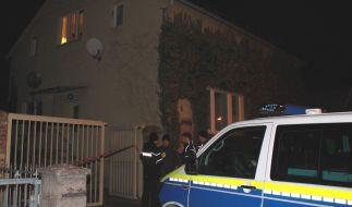 Ein Polizeiauto und Polizisten stehen vor dem Grundstück, auf dem ein Mann erschossen wurde. (Foto)