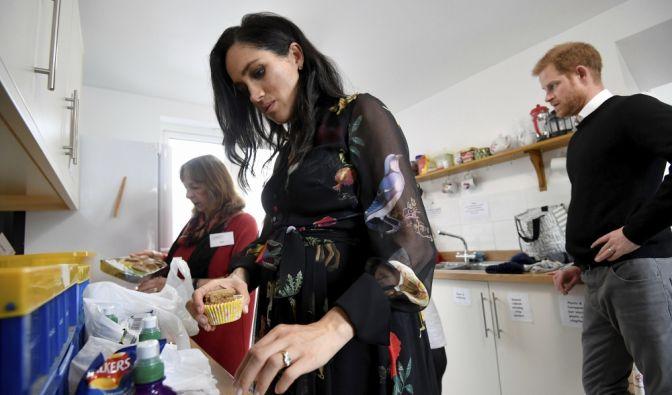 Der britische Prinz Harry (r) und seine Frau, Herzogin Meghan (M), helfen während ihres Besuchs bei der Hilfsorganisation für Frauen, One25, bei der Vorbereitung von Essenspaketen.
