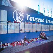 Zahlreiche Trauerkerzen stehen an der Tausend-Freunde-Mauer vor der Veltins Arena.
