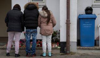 Trauernde Nachbarn und Freunde der Familie des Opfers stehen vor dem Haus, in dem die Tochter der Familie von ihrem Freund umgebracht worden war. (Foto)