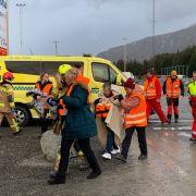 Passagiere des Kreuzfahrtschiffes Viking Sky werden in eine Notunterkunft gebracht, nachdem sie mit einem Hubschrauber vom Schiff geholt wurden.