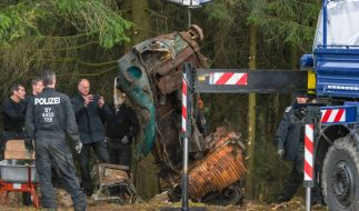 Einsatzkräfte der Polizei heben mit einem Kran ein Auto aus einem möglichen Ablageort einer Mädchenleiche. (Foto)
