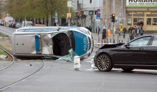 Der umgekippte Streifenwagen liegt nach einem Zusammenstoß mit einem Pkw auf einem Grünstreifen am Frankfurter Tor. (Foto)