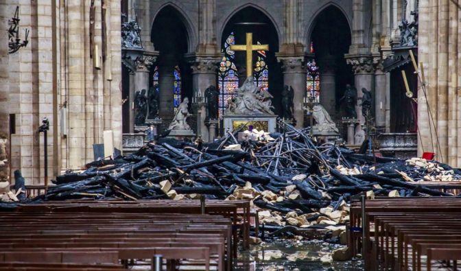 Trümmerteile und verkohlte Holzbalken liegen im Inneren der Kathedrale Notre-Dame. (Foto)