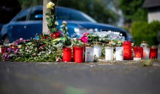 Blumen und Kerzen stehen an der Stelle in Moers, an der eine unbeteiligte Frau bei einem mutmaßlichen illegalen Autorennen verletzt und später gestorben ist. (Foto)